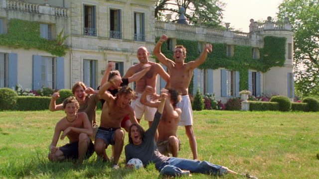 vídeos y material grabado en eventos de stock de wide shot group of young men cheering with chateau in background / france - sin camisa