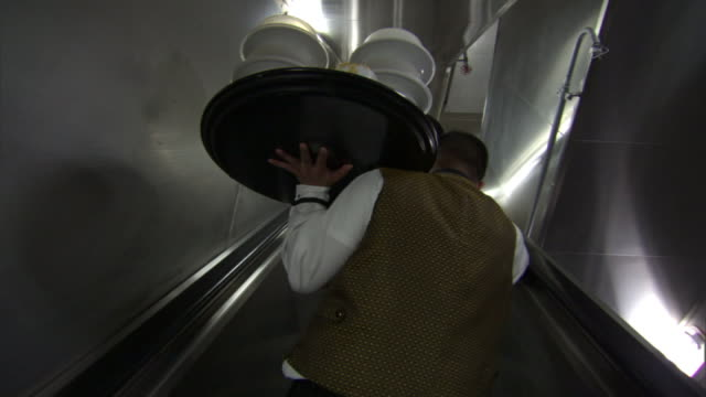 wide shot hand-held push-in - a waiter with a tray of dishes ascends escalators toward a restaurant. / new orleans, louisiana, usa - 盆点の映像素材/bロール