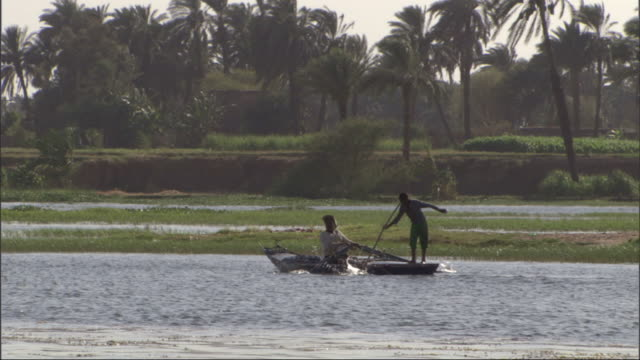 wide shot, hand-held tracking-left - young men fish from a small rowboat / egypt - backwater stock videos & royalty-free footage