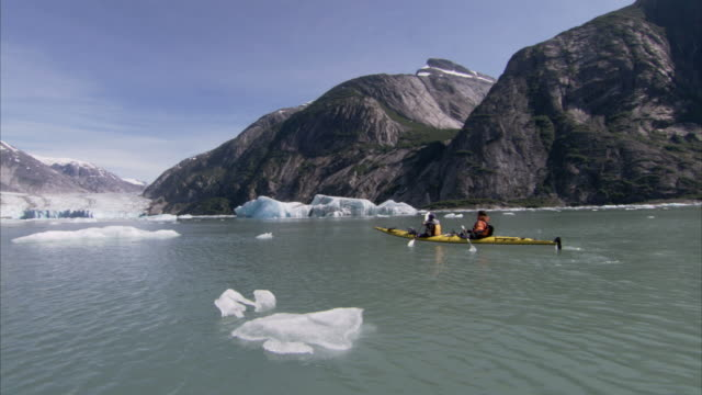 'Wide Shot hand-held-Kayakers paddle through icy waters along Alaska's glacial shore. / Alaska, USA'