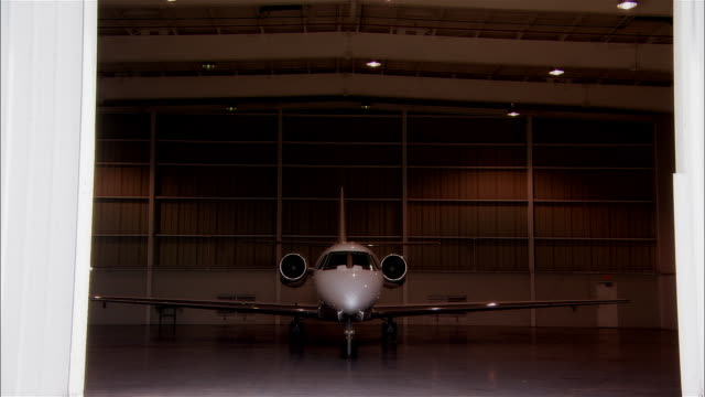 wide shot hangar door closing in front of private jet at opa locka airport/ miami, florida, usa - 飛行機格納庫点の映像素材/bロール