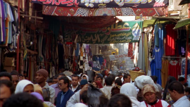 Wide shot heads of people walking in crowded street bazaar in old section / Cairo, Egypt