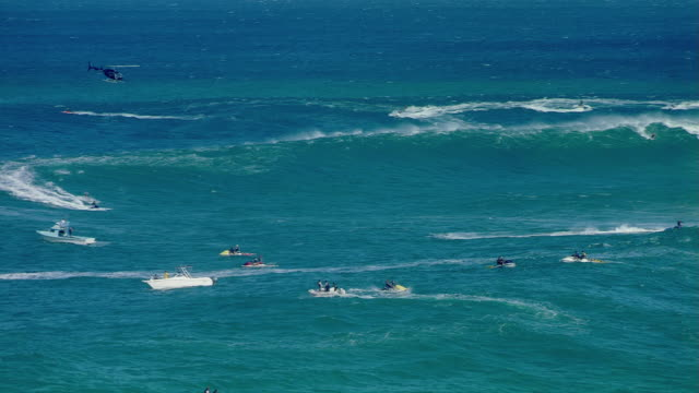 Wide shot Helicopter hovering above extreme surfing world champion Garrett McNamara and other surfers in sea/ Tahiti