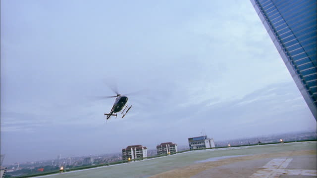 wide shot helicopter landing on building rooftop - helicopter stock videos and b-roll footage