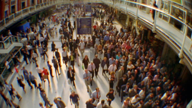 Wide shot high angle crowd of commuters walking in Liverpool Street Station / London, England