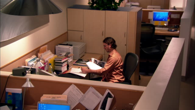 wide shot - high angle man writing in notebook and working late in empty office - desktop pc stock videos & royalty-free footage