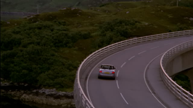 wide shot high angle panning from  convertible driving on bridge over lake to picturesque mountain scene reflected in lake/ scotland - オープンカー点の映像素材/bロール