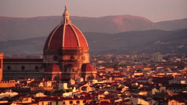 wide shot high angle pan tilt up tilt down rooftops of florence to santa maria del fiore (duomo) /  mountains in background - florence italy stock videos & royalty-free footage