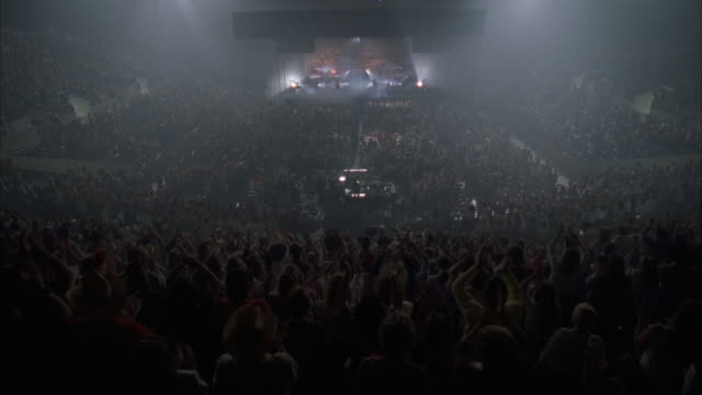 wide shot high angle view of band performing in large arena / crowd clapping in foreground - dry ice stock videos & royalty-free footage