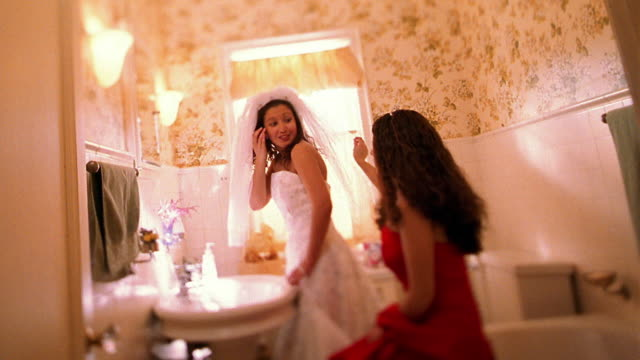 vídeos de stock, filmes e b-roll de wide shot hispanic bridesmaid helping hispanic bride get ready in bathroom - bridesmaid