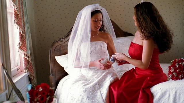 Wide shot Hispanic bridesmaid in red dress giving Hispanic bride handkerchief