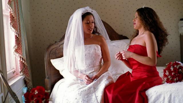 Wide shot Hispanic bridesmaid in red dress giving Hispanic bride necklace