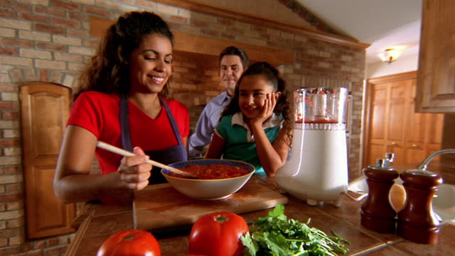 vídeos y material grabado en eventos de stock de wide shot hispanic father tasting tomato sauce with hispanic mother and daughter in kitchen - sauce