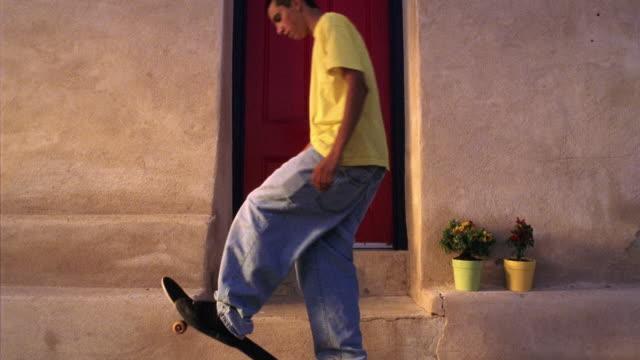 Wide shot Hispanic teenage boy skateboarding up to doorway and sitting down on step / Tucson, Arizona