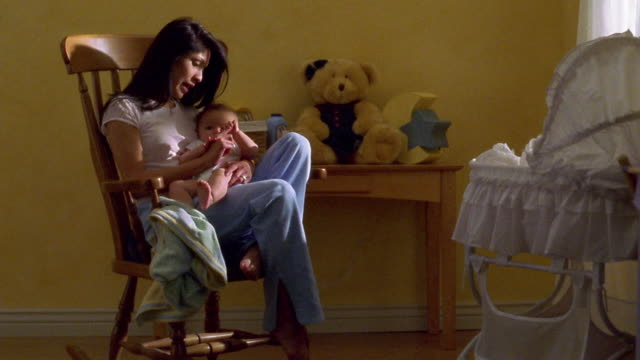 wide shot hispanic woman in rocking chair playing with baby on her lap - rocking chair stock videos & royalty-free footage