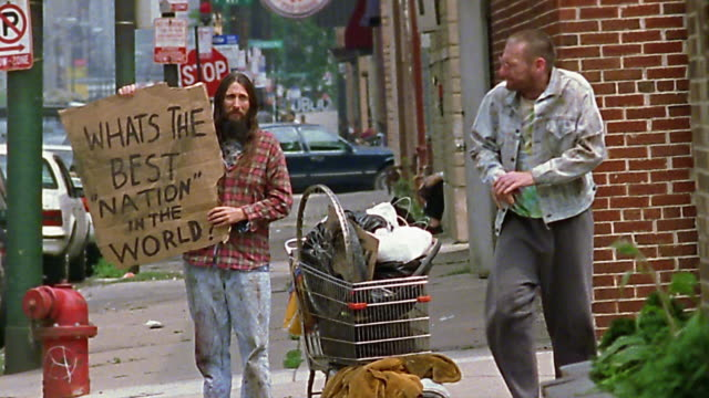 "stockvideo's en b-roll-footage met wide shot homeless man with sign that says ""whats the best nation in the world?"" / other homeless man passing - chicago illinois"
