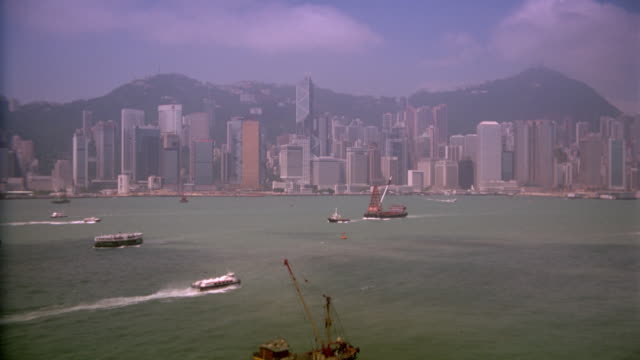 wide shot PAN of Hong Kong skyline and harbor with boats