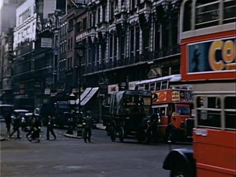 1939 Wide shot Horse carriage traveling on crowded city street alongside double-decker buses and black taxis / London, England