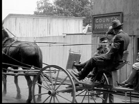 stockvideo's en b-roll-footage met 1913 b/w wide shot horse cart and passengers arriving outside county poor house entrance / usa  - paardenkar