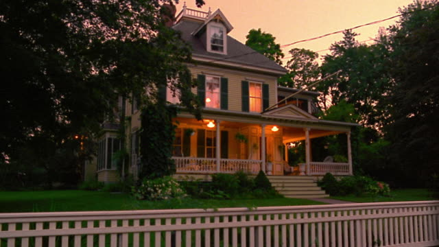 wide shot PAN house + porch lights turning off in suburban house with white fence in foreground at dusk