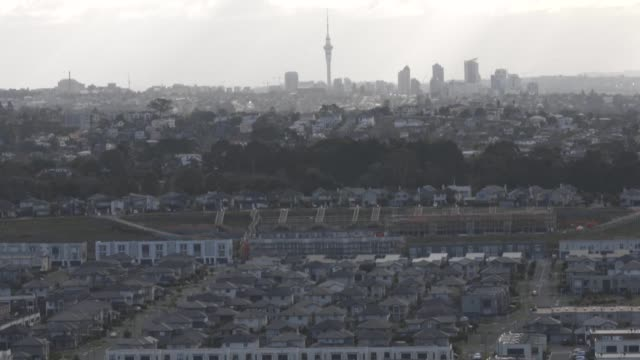 wide shot, houses stand in the suburb of mount wellington as the sky tower stands in the distance in auckland, new zealand, wide shot, pan left to... - new zealand culture stock videos & royalty-free footage