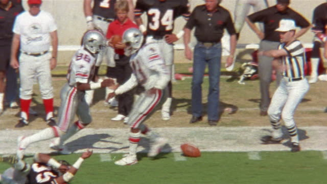 1985 Wide shot Houston Gamblers player Mike Mitchell tackling Tampa Bay Bandits player at sideline during game / USA