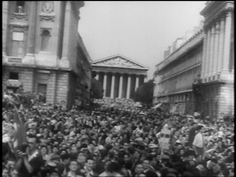 B/W 1944 wide shot huge crowd in streets at Liberation of Paris / columned building in background / documentary