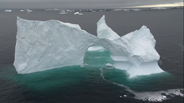 wide shot ice formation with natural arch floating in antarctic sea/ antarctica - antarctica melting stock videos & royalty-free footage