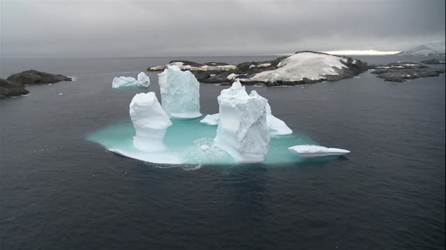 wide shot ice formations floating near glacier along coast of antarctic sea/ antarctica - antarctica melting stock videos & royalty-free footage