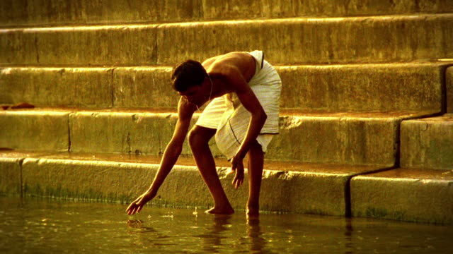 vidéos et rushes de wide shot indian man standing on stairs (ghat) washing face in ganges river / varanasi, india - sale