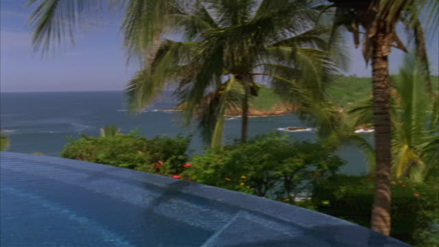 wide shot infinity pool overlooking pacific/ pan across pool and palm trees to resort/ costa careyes, mexico - infinity pool stock videos & royalty-free footage