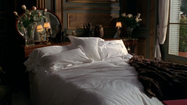 Wide shot interior of bedroom with fur coat thrown on top of bed