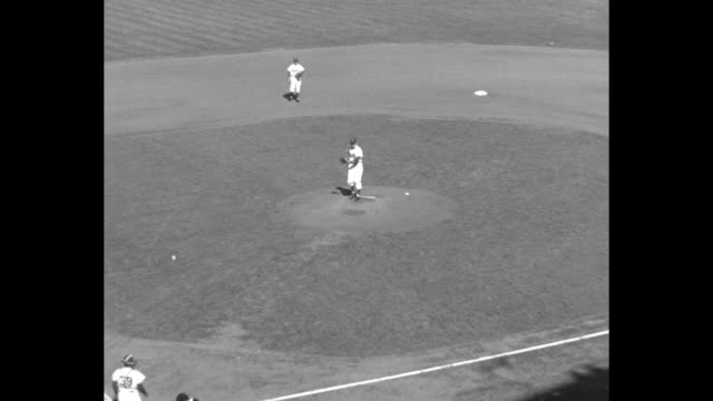 Wide shot interior of Ebbets Field with stands packed / high angle long shot of Billy Lowes Dodgers pitcher on mound / zoom in to Lowes' wind up and...