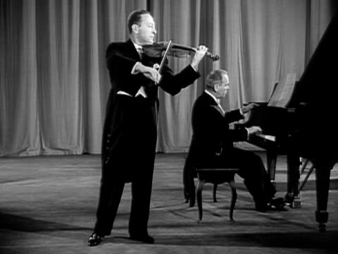Wide shot Jascha Heifetz playing violin onstage next to pianist during performance/ USA