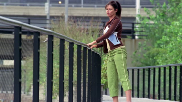 wide shot jogger stretching against railing / milwaukee, wisconsin - tracksuit bottoms stock videos & royalty-free footage