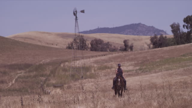 wide shot, karen, closer to camera, rides horse rolling hills pastures, windmill and mountain peak in background - hat stock videos & royalty-free footage