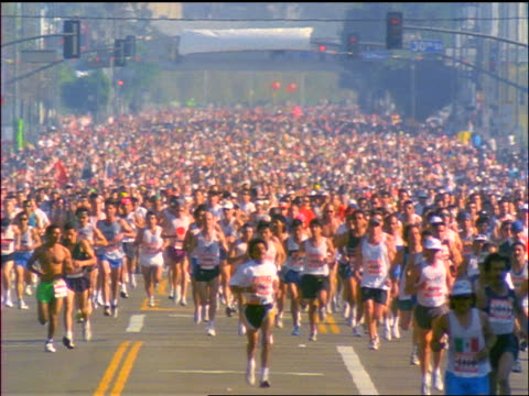 vídeos de stock e filmes b-roll de wide shot large crowd of people running in marathon toward camera on city street / los angeles marathon - 1990
