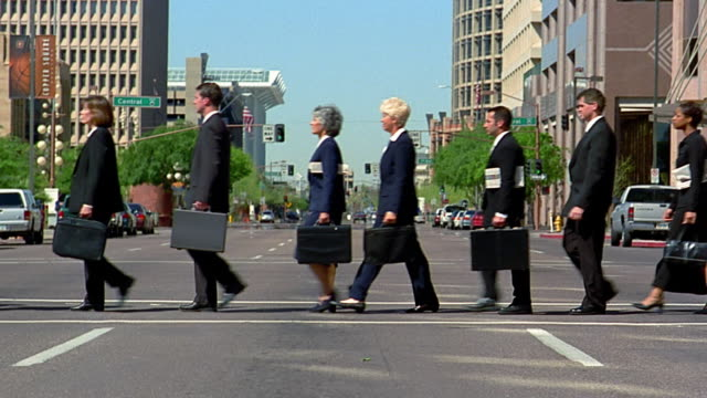wide shot large group of business people walking single file across intersection - briefcase stock videos & royalty-free footage