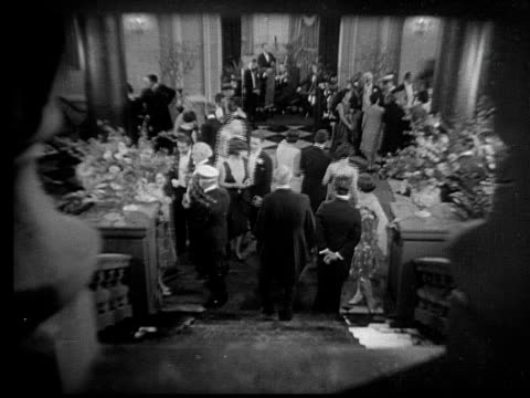 vidéos et rushes de 1928 b/w wide shot large group of men and women attending evening ball and wearing evening gowns and tuxedos / usa  - 1928