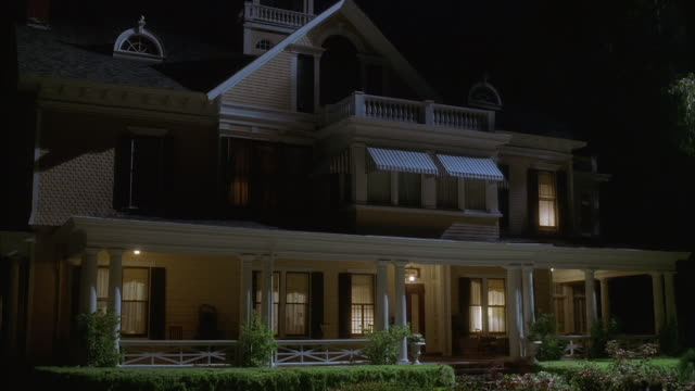 wide shot large house with lights on at night - veranda stock videos & royalty-free footage