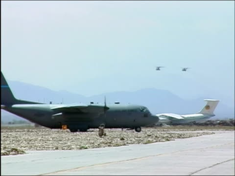 Wide shot large military airplane taxiing on runway as two military helicopters fly overhead at Bagram Air Base / Bagram Afghanistan / AUDIO