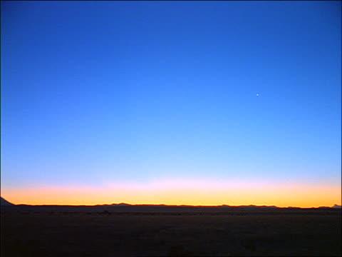 vídeos de stock, filmes e b-roll de wide shot large sky at sunset/sunrise over silhouette of desert or plains / west texas - céu romântico