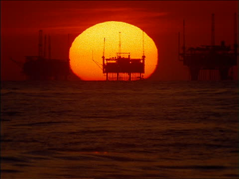 wide shot large sun behind silhouetted offshore oil rigs at sunset / santa barbara, california / filter - platform stock videos & royalty-free footage