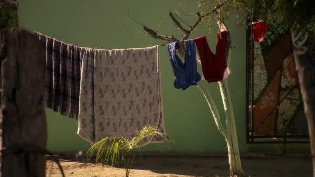 vídeos y material grabado en eventos de stock de wide shot laundry hanging out to dry on clothesline - cuerda de tender la ropa