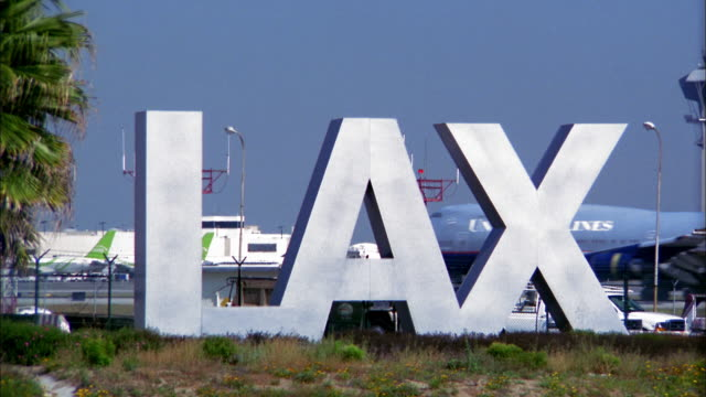 wide shot lax airport sign and airplane taxiing in background - lax airport stock videos & royalty-free footage