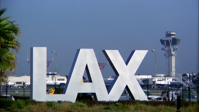 wide shot lax airport sign and traffic control tower / airplane taking off in background - lax airport stock videos & royalty-free footage