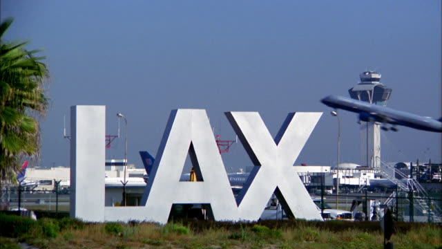 wide shot lax airport sign and traffic control tower / airplane taking off in background - 2004 stock-videos und b-roll-filmmaterial