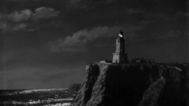 B/W wide shot lighthouse on cliff with revolving spotlight at night