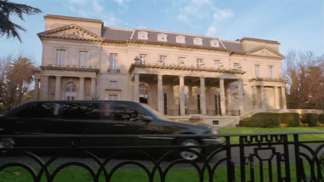 wide shot limousine driving past mansion - limousine luxuswagen stock-videos und b-roll-filmmaterial
