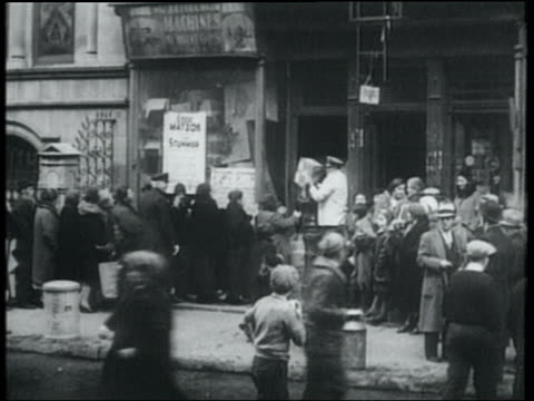 vídeos de stock e filmes b-roll de b/w 1932 wide shot line of people receiving free matzos from store / lower east side, nyc - 1930